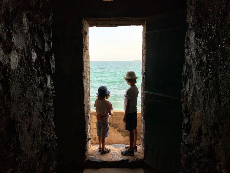 Två barn står i en stenport med hav i bakgrunden.