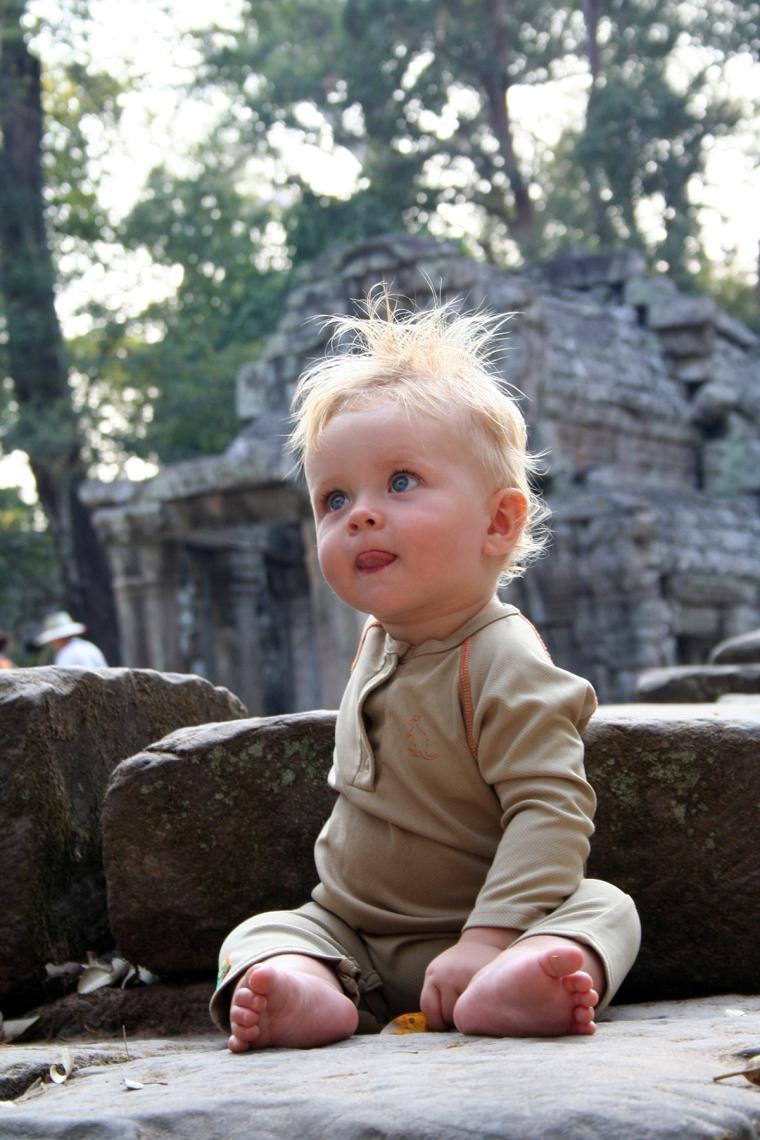 En bebis sitter på en sten med en tempelruin i bakgrunden.