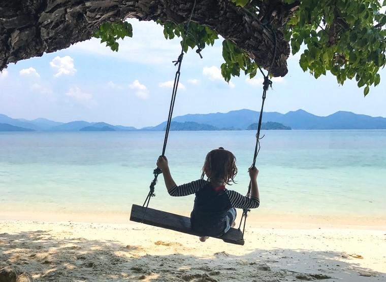 Ett barn på en gunga på en strand.