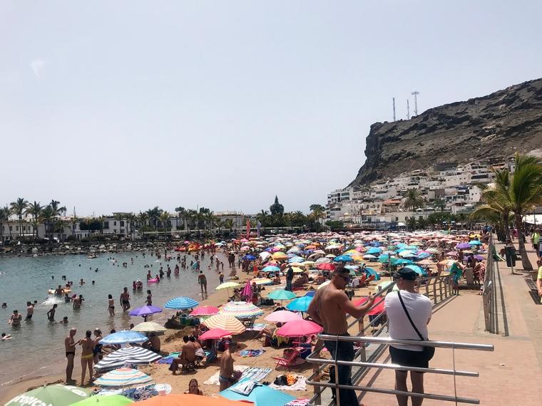 En sandstrand packad med folk och parasoller.