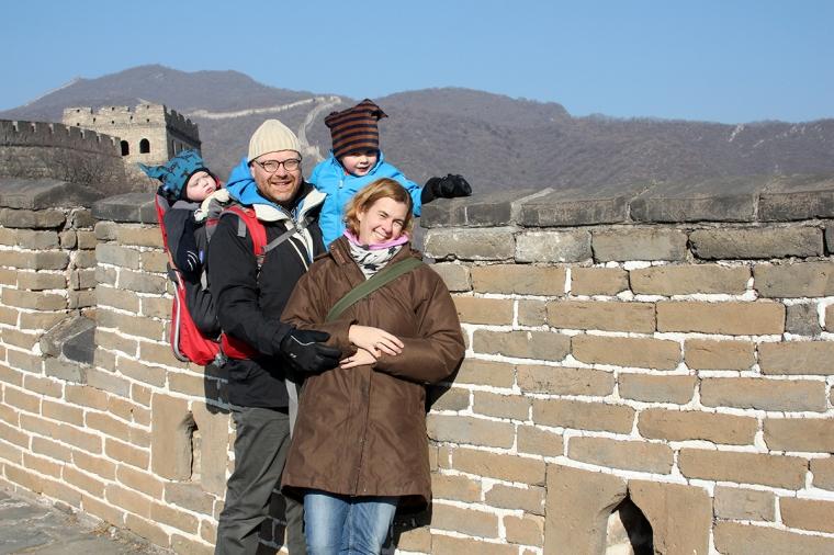 Två vuxna och två små barn poserar på en lång brun mur.