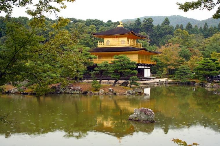 Ett hus i asiatisk stil klätt med bladguld. Huset ligger vid en liten sjö.
