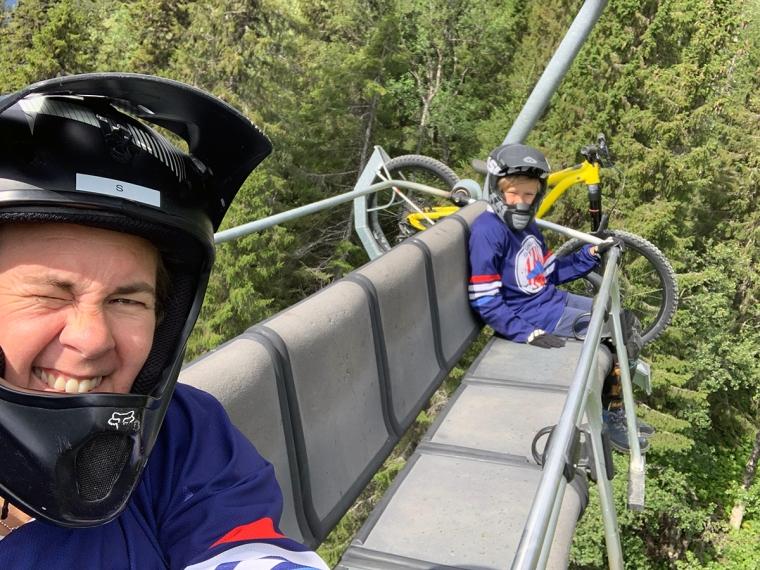 Två personer och en cykel i en sittlift.