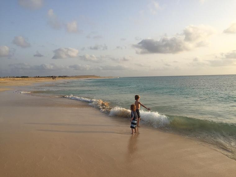 Två barn leker i vågorna i vattenbrynet på en öde strand.