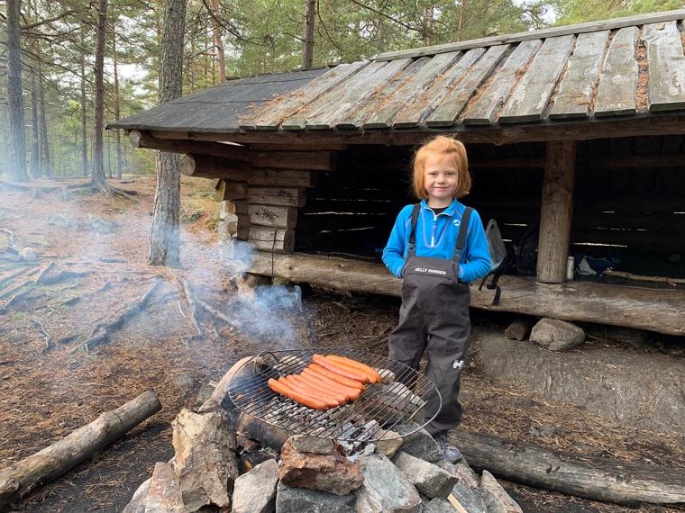 Ett barn bakom en eld med korv som grillas.