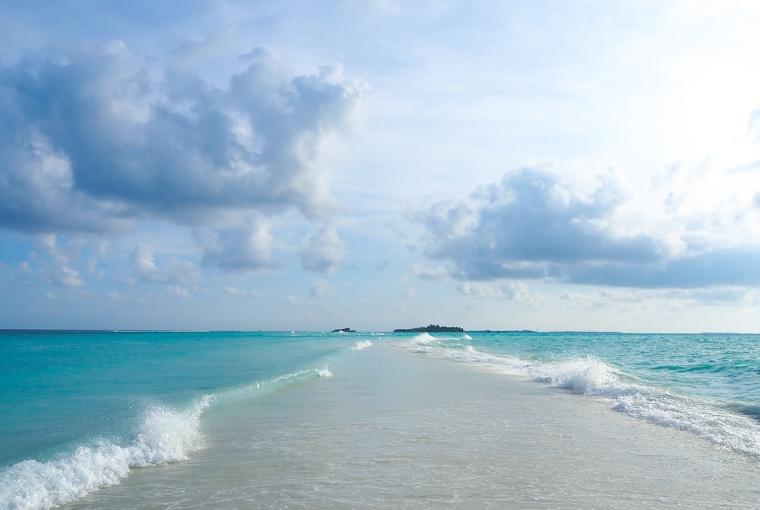 En trandremsa med hav på båda sidor och en ö långt i bakgrunden.