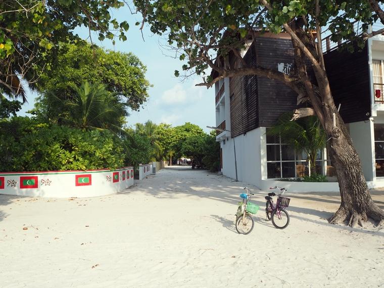 En gata gjord av sand med ett litet hotell.