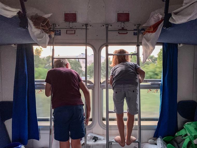 Två barn stpr i fönstret i en tågkupé.