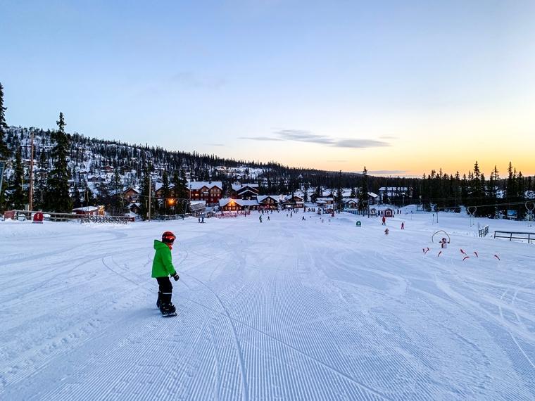 Ett barn på snowboard i en skidbacke.
