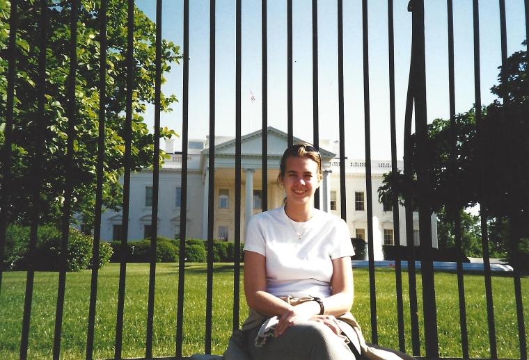 En kvinna framför vitahuset.