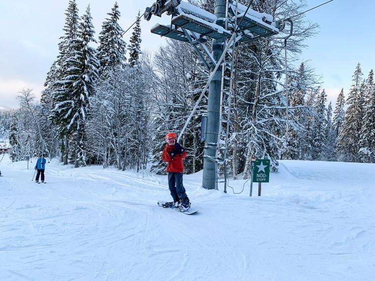 Ett barn åker snowboard i en knapplift.