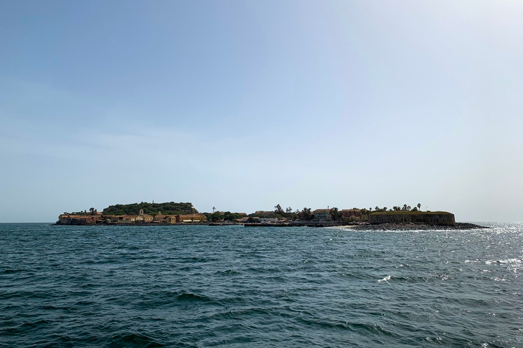 En ö med lite bebyggels med hav runt omkring.