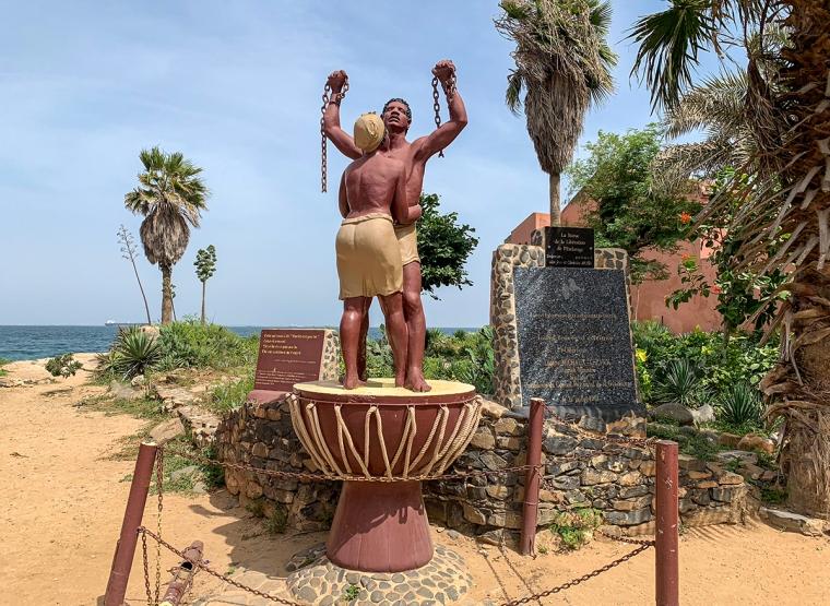 En staty där en man sträcker upp sina armbar där det hänger kedjor och en kvinna kramar om honom. Båda står på en trumma.