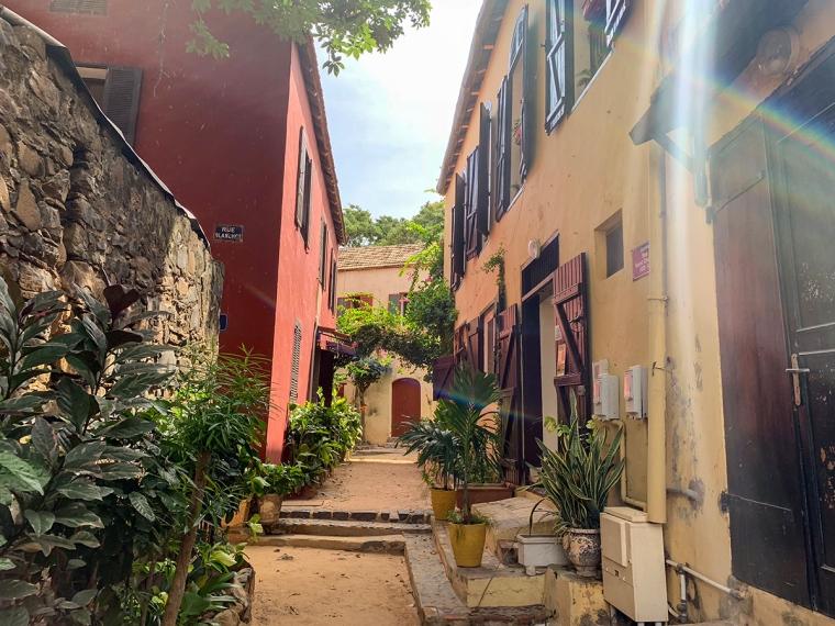 En gränd med färgglada hus och växtlighet.