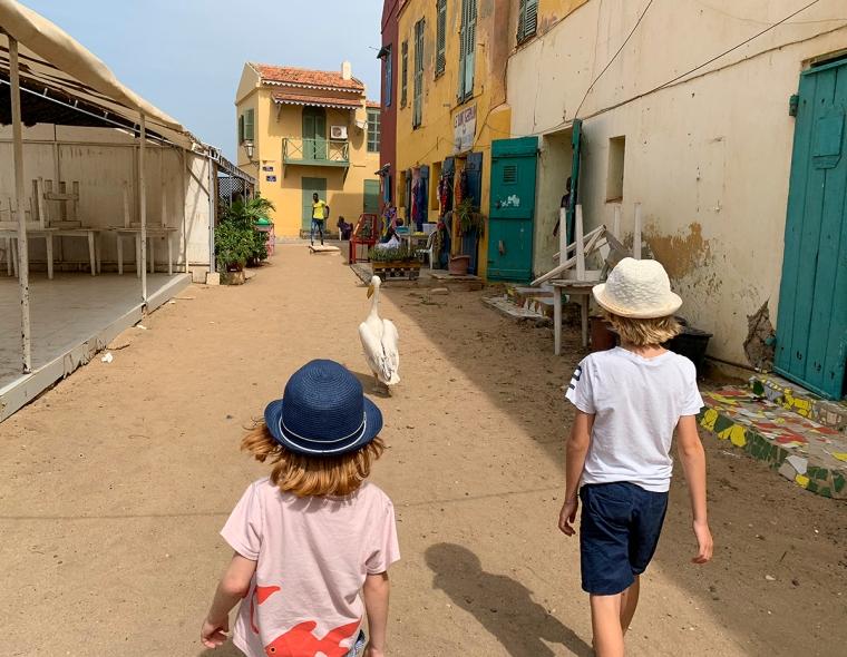 En pelikan går före två barn på en gränd med färgglada hus.