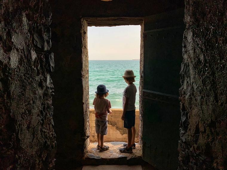 En sentvägg med en dörröppning där det står två barn och man kan se havet direkt utanför.