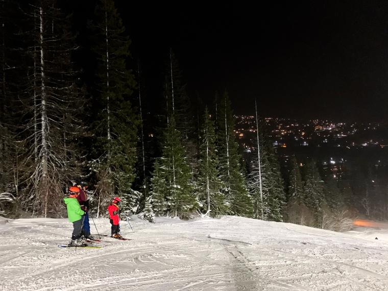 En vuxen och två barn står i en slalombacke som är upplyst av strålkastare.