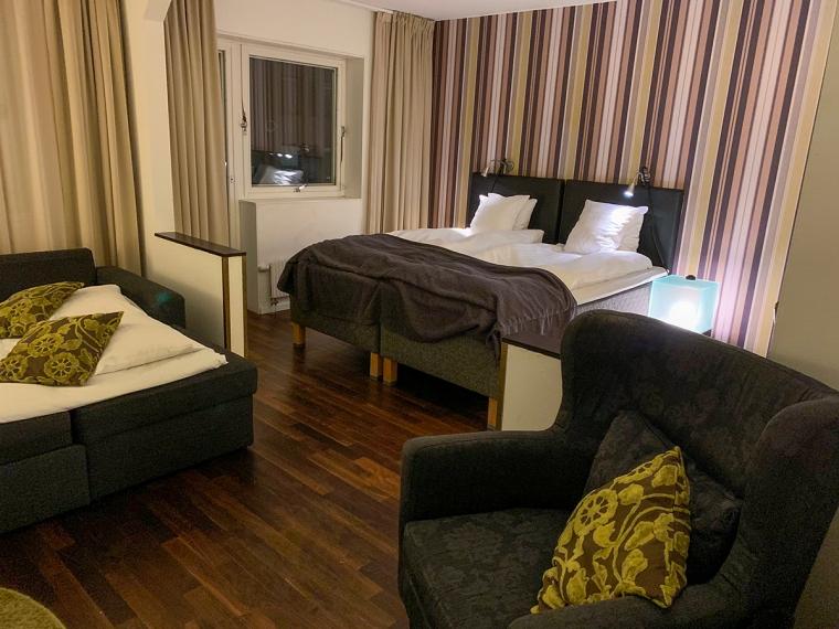 Ett hotellrum med en dubbelsäng, en bäddsoffa och en fåtölj.