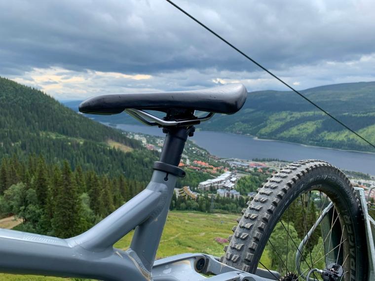 En smal cykelsadel på en cykel som åker lift med utsikt mot berg och sjö.