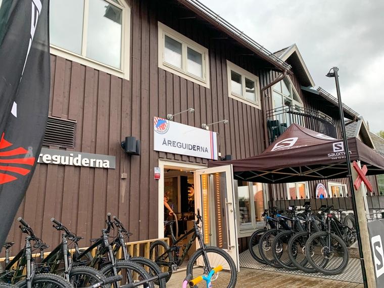 Ett brunt hus med cyklar utanför och en skylt med texten Åreguiderna.