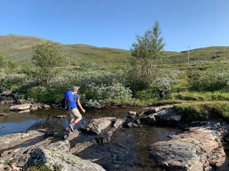 Ett barn går över stenar i ett vattendrag.