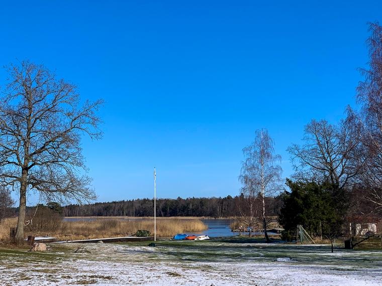 En gräsmatta med lite snö och en blå sjö i bakgrunden.