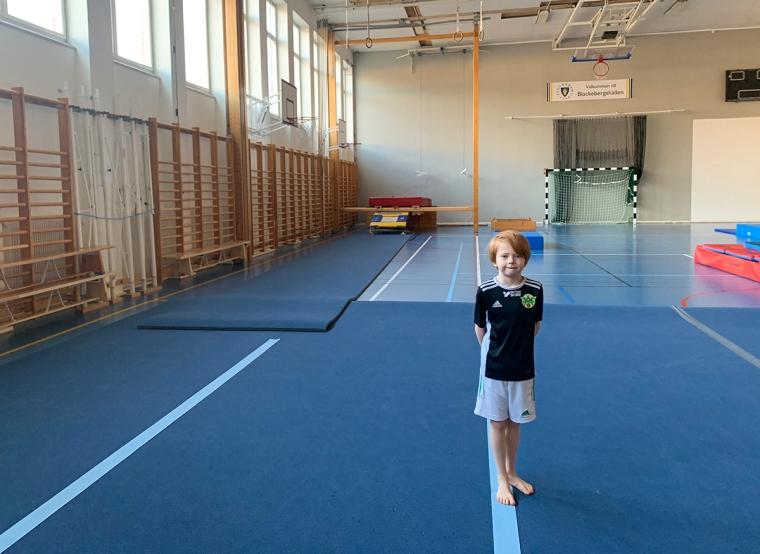 Ett barn står ensam i en gymnastikhall.
