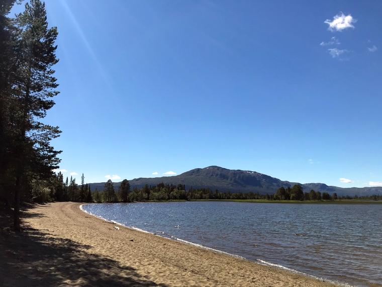 sandstrand med blått vatten och berg i bakgrunden.