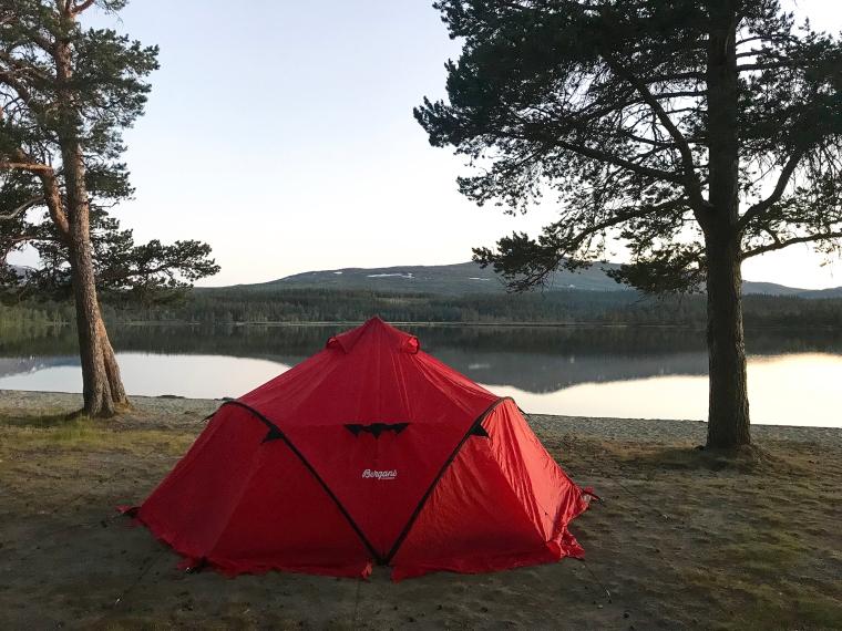 Tält på en strand med berg i bakgrunden.