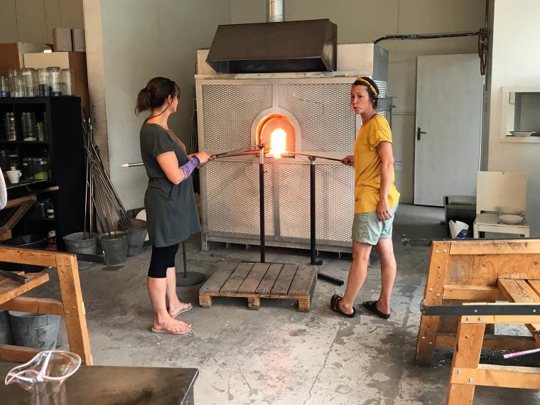 Två kvinnor arbetar i en glashytta.