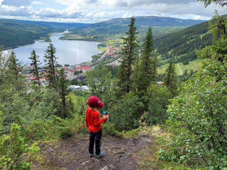 Ett barn dricker vatten med utsikt över Åre och Åresjön.