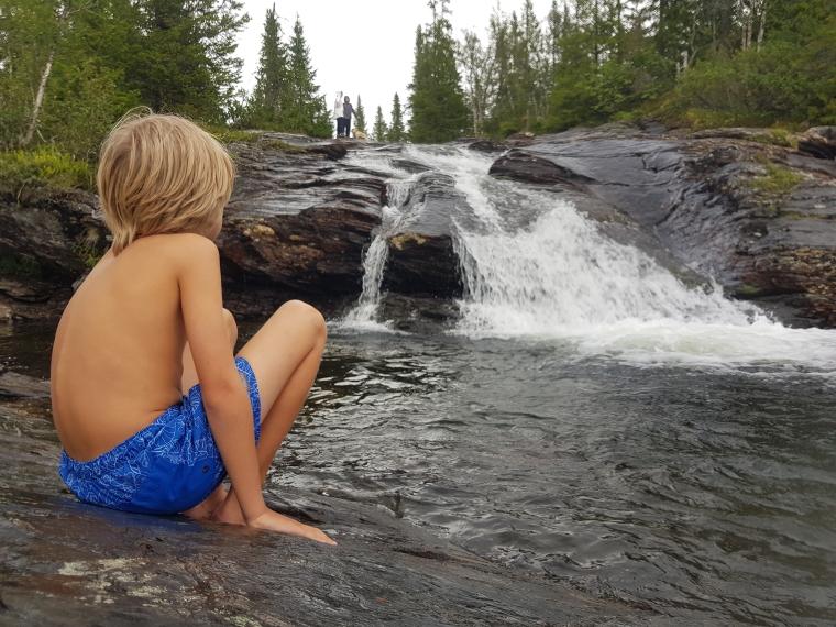 Ett barn sitter vid ett litet vattenfall.