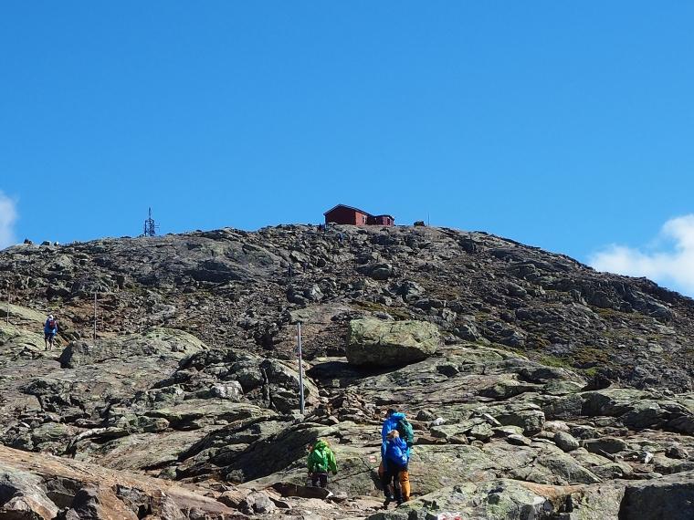 En vuxen och två barn vandrar upp för ett berg mot en röd stuga på toppen.