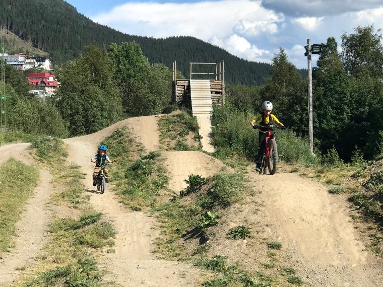 Två barn på cykel i en dirt park.