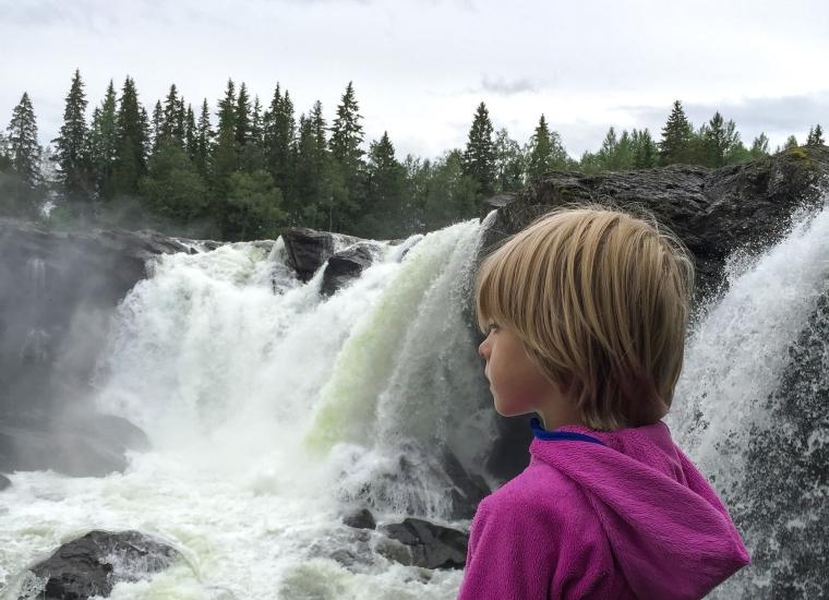Ett barn står och blickar ut över ett högt och vilt vattenfall.