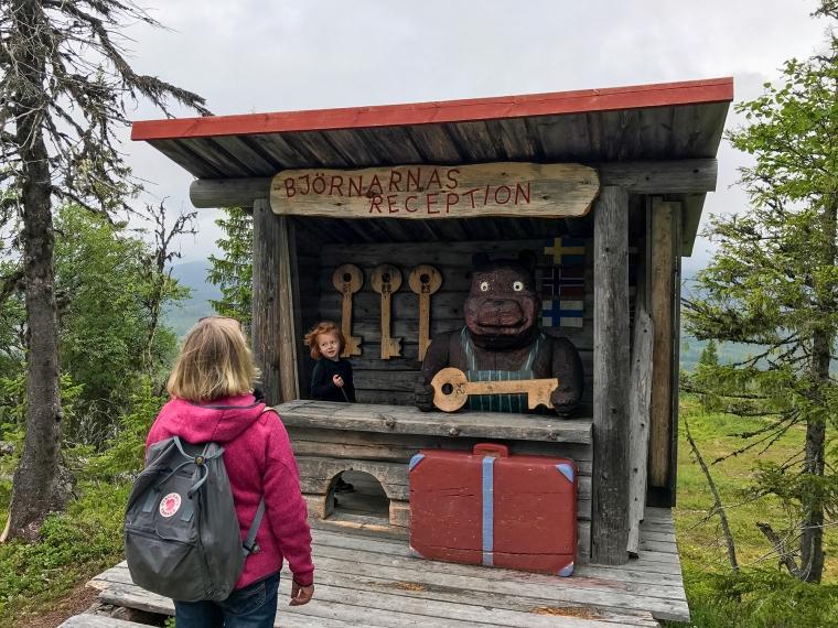 Ett barn leker i en trädkoja utformad som en reception inkl en stor träbjörn.