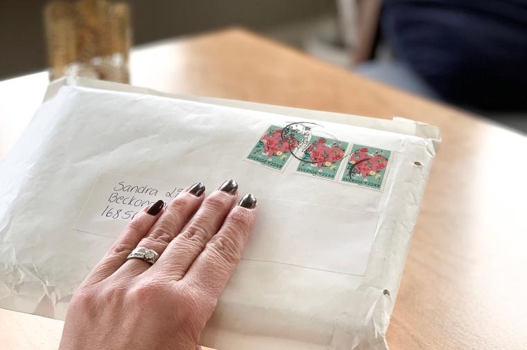 Ett adresserat paket med tre frimärken.