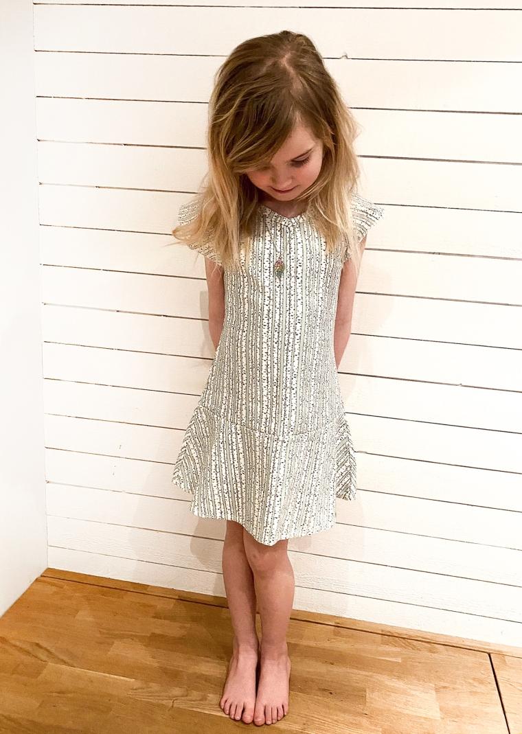 En flicka i en klänning med björkstammar i tyget.