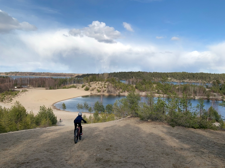 Ett barn på cykel som cyjklar ner för en sandbacke.