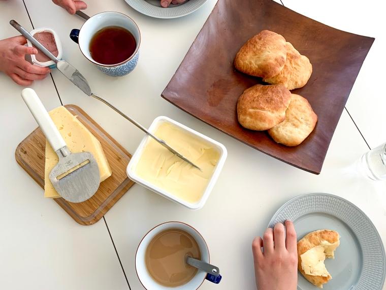 Ett dukat bord med tekakor, smör, ost och temuggar.