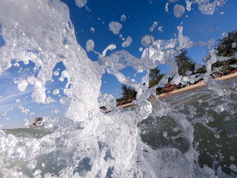 Närbild på vattenstänk med en strand i bakgrunden.