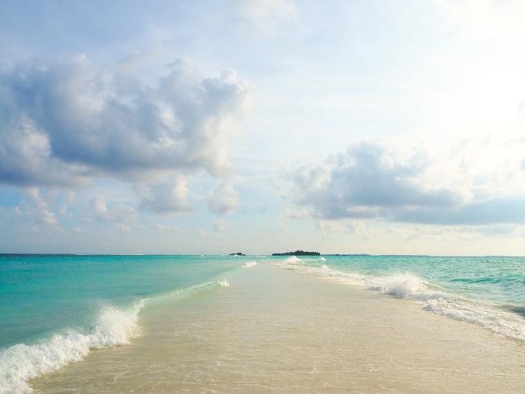 En strandremsa med hav på båda sidor.