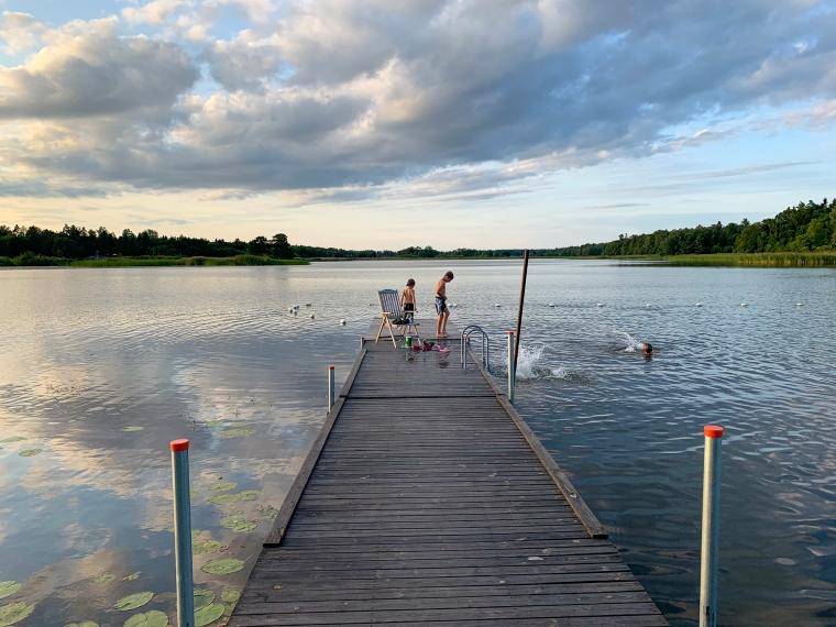 Två barn på en brygga, redo att bada.