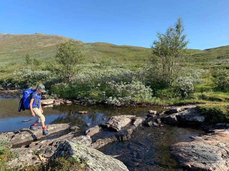 Ett barn med ryggsäck gör på stenar över ett vattendrag.