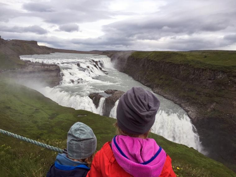Två barn som tittar på ett stort vattenfall.