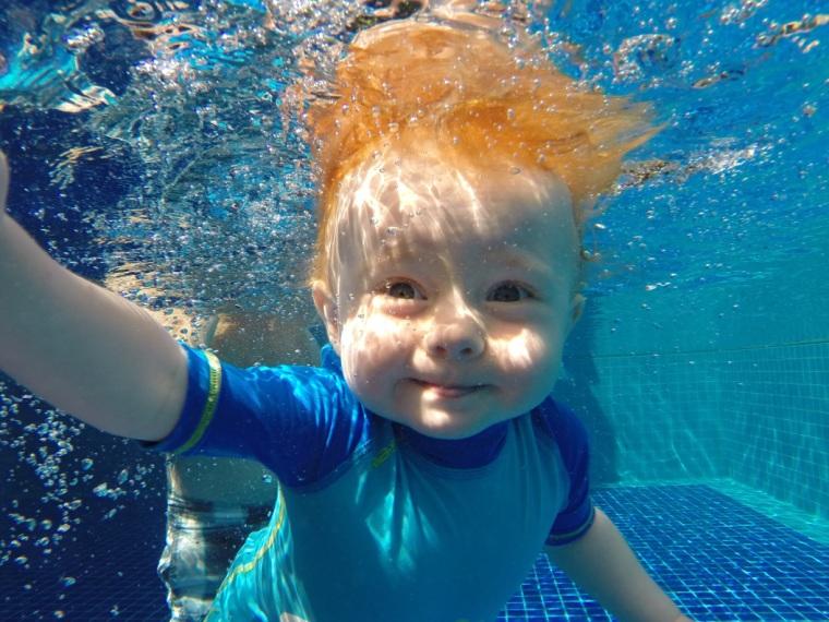 En bebis simmar under vattnet.