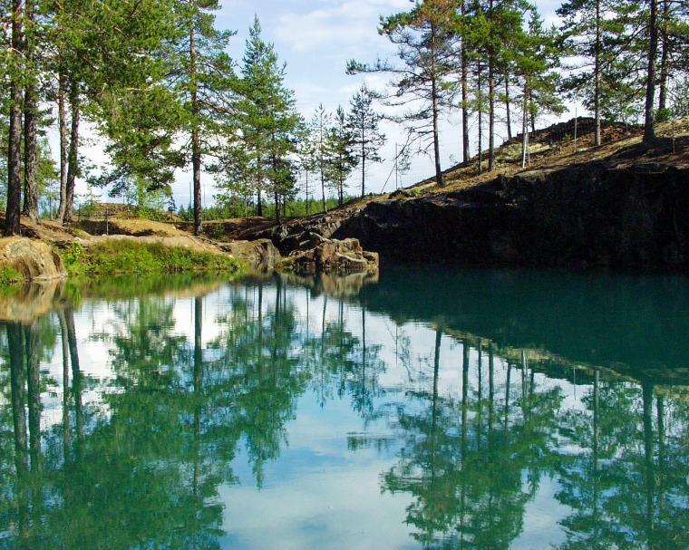 En vattenfylld gruva med barrträd runt kanten.