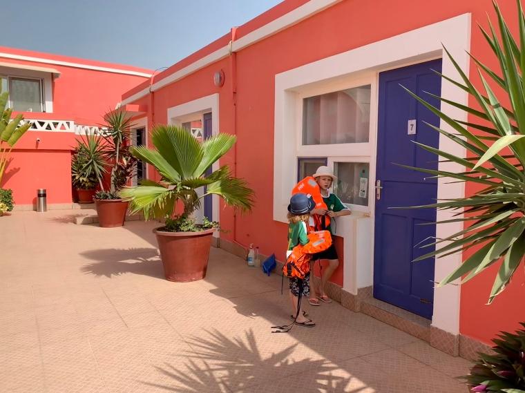Två barn som står utanför en blå dörr med nr 7.