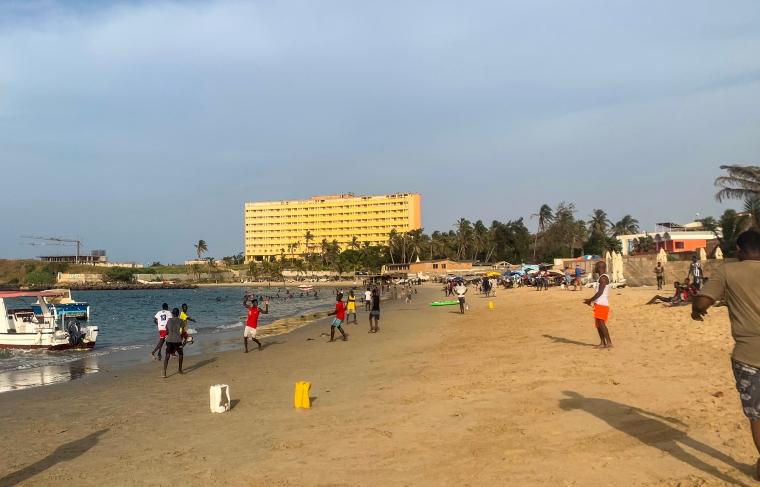 Ett gäng killar spelar fotboll på en strand med plastdukar som mål.
