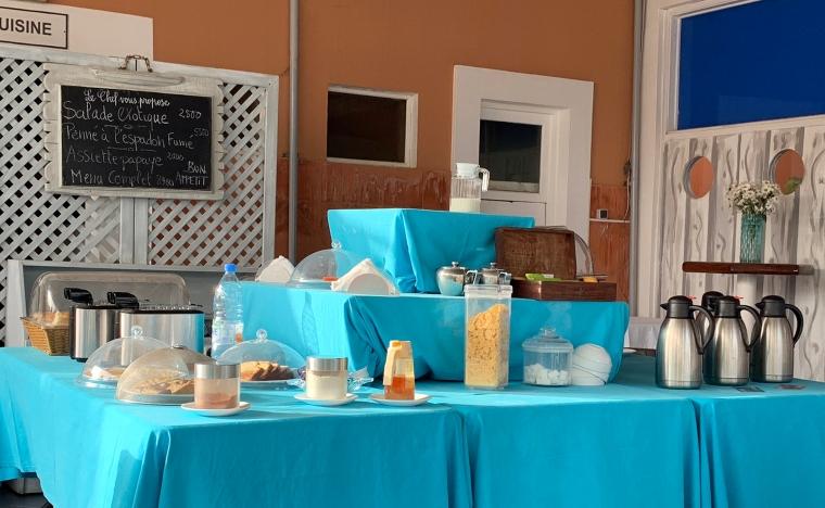 Ett bord med en enkel uppdukad frukostbuffé, rostbröd, kaffe, tea, flingor, mjöl och lite frukt.